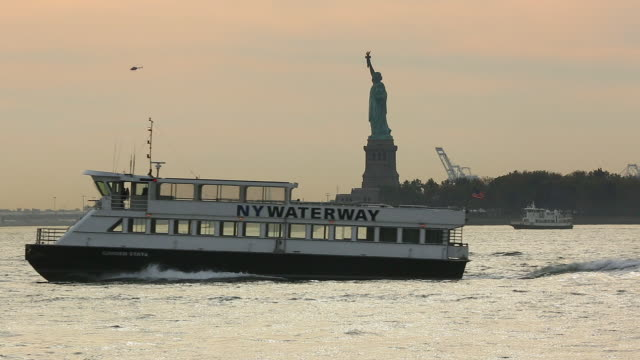 Camera captures boats and yacht which run on brilliant New York Bay at sunset. Statue of Liberty can be seen behind.