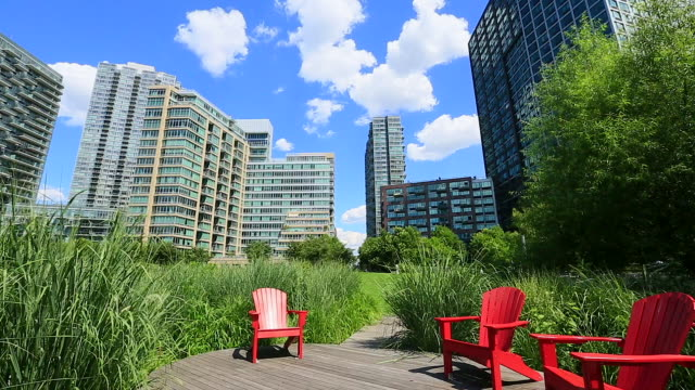 PAN Camera captures chairs and new highrise residences at grassy boardwalk at Long Island City Queens New York.