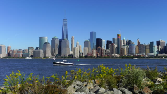 Camera captures Manhattan skyscrapers and ships run on Hudson River from Liberty State Park.