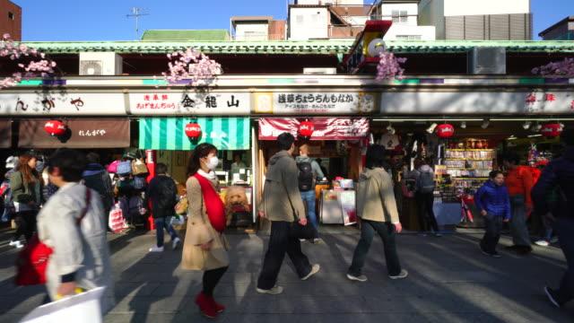 Camera captures many people and traditional gift shops along the Nakamise-dori at Sensoji Temple (Asakusa Kannon Temple).