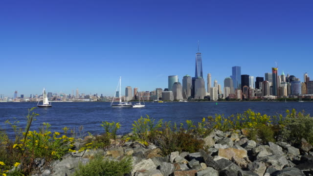 PAN Camera captures New Jersey waterfront high-rise residential buildings and ships from Liberty State Park. Manhattan skyscrapers can be seen at opposite shore of Hudson River.