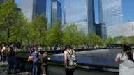 TU Camera captures the Memorial South Pool and people at 911 Memorial Park which are surrounded by fresh green trees.World Financial Center and other skyscrapers can be seen behind.