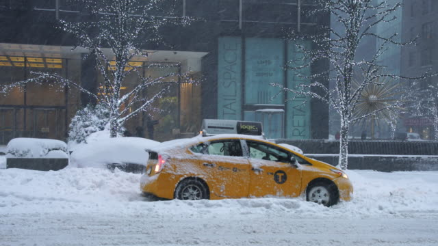 Camera captures traffic of 6th Avenue during the serious winter snowstorm Jonas.Road and cars were covered by snow and visibility is bad for snowing.Taxi tires are slip in the deep snow and car is stuck.