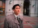 Camera circles Asian businessman in raincoat standing outside of Municipal Building / NYC