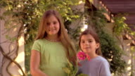 Camera drifts down to a portrait of two girls holding a potted gerber daisy.