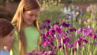 Camera drifts down to two girls looking at irises in a garden.