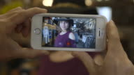 camera films phone while girl tries on hat for fashion blog