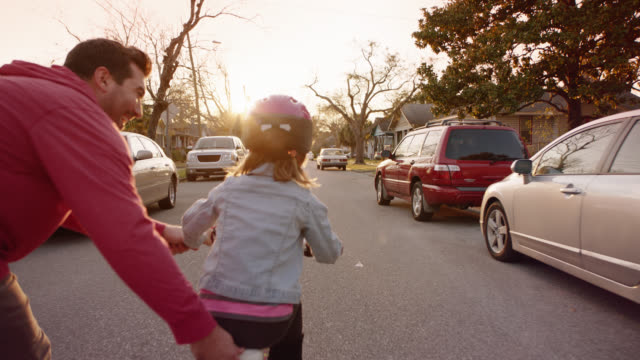 WS SLO MO. Camera follows behind as father teaches daughter to ride bike on neighborhood street.