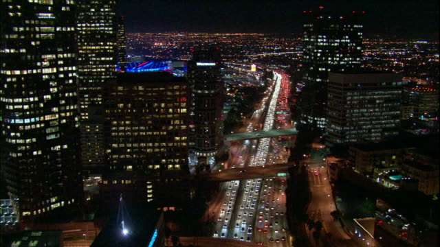 Camera glides  souhward through corridor of downtown LA skyscrapers above 110 freeway, reveals Staples center in distance.