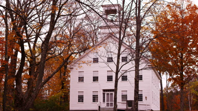 Camera pans across old Vermont meeting hall in forest of Fall colored trees.