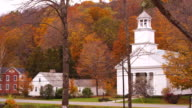 Camera pans across old whitewashed Vermont church surrounded by Fall colored trees.