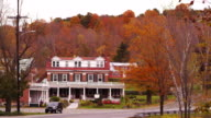 Camera pans across quaint Vermont Bed & Breakfast surrounded by Fall colored trees.