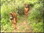 Camera pans as Yanomami Indians walk past carrying wood in the Amazon rainforest