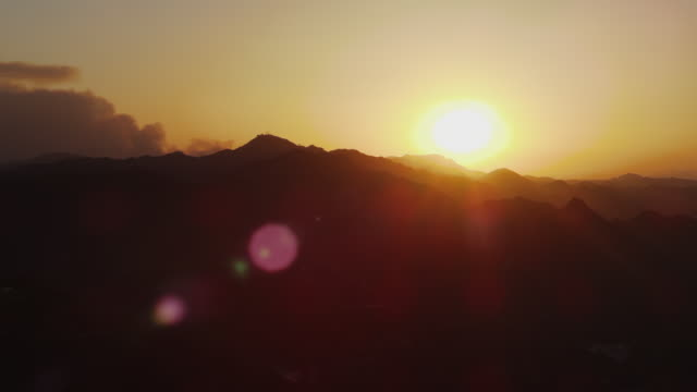 Camera pans Malibu Mountains, golden setting sun just above ridgeline, smoke from distant brush fire billows up from behind far peak