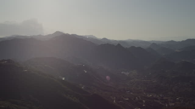 Camera pans Malibu Mountains, smoke from distant brush fire billows up from behind far peak, sun flares lens