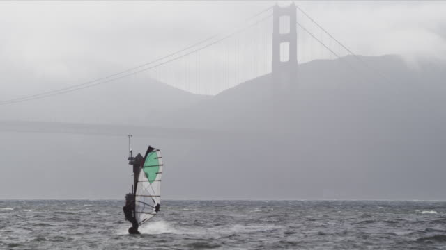 Camera pans with windsurfer sailing on San Francisco Bay near Crissy Field, Golden Gate Bridge north tower in background