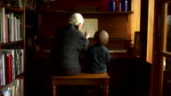 Camera pulls back slowly on grandmother and grandson playing piano.