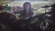 Camera pushes in on female mechanic working on motorcycle with ratcheting socket wrench in garage.