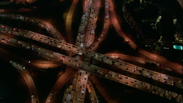Camera rotates above a cloverleaf freeway exchange; the intertwining roads, moving cars, and rotating camera combine to create a kaleidascopic effect.