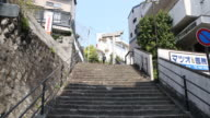 A camera tilt up showing young people going down the stone stairs and the onelegged torii at the top a standing remain of the Sanno shrine which...