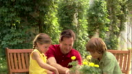 Camera tilts down to a father helping his children plant flowers in pots.