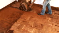 Camera tilts up to see a woman operating a big old drum floor sander