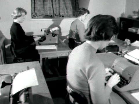 Camera tracks along two rows of young women seated at desks and typing at the BBC secretarial school 1959