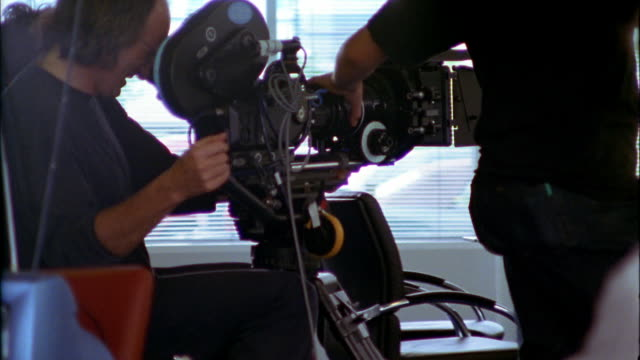 Cameramen on a dolly film an office scene.