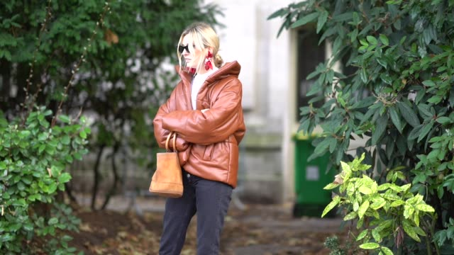 Camille Charriere wears sunglasses a brown leather puffer coat black pants red shoes a brown cylinder shaped bag outside Moncler during Paris Fashion...