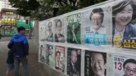 Campaign posters of South Korean presidential candidates are displayed on a wall in Incheon South Korea on Monday May 8 A pedestrian walks past...