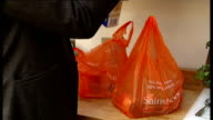 Campaign to cut sugar consumption ENGLAND London EXT Reporter towards from supermarket with shopping bag and piece to camera Products containing...