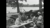 Campers feed bear from Model T Ford car / campers pull up in Model T Ford and trailer set up tent at camp / campers set up lunch table / family has...