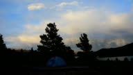 Camping Tent Stands alone as the Sun sets and clouds build Alpine glow comes out the colors of the evening set into the Colorado Background