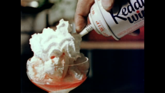 Can of 'Reddi Wip' dispenses whipped cream over bowl of ice cream / chocolate syrup poured over mousse style dessert on plate Whipped cream and...