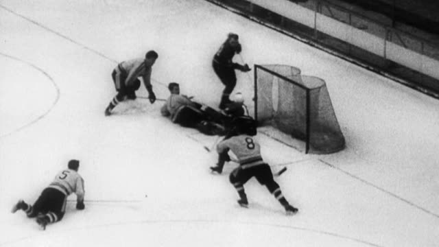 Canadian hockey team Trail Smoke Eaters defeats USSR at world hockey finals / players skate around trying to get puck / Canadians dominate game /...