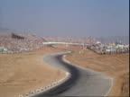 CanAm race cars racing along esses at Riverside International Raceway / 1965 Pontiac Grand Prix pace car driving along racetrack / race car driver...