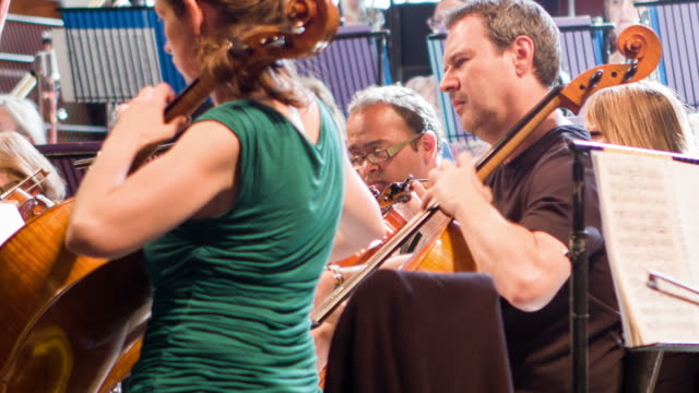 Candid cellists and viola player in orchestra