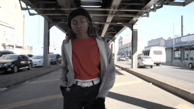 A candid portrait of a young, black woman in her twenties with her skateboard in Brooklyn, NYC-4k