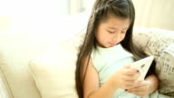 Candid shot of young girl using smartphone on sofa Full HD.