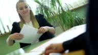 Candidato dando documenti per l'intervistatore alla reception
