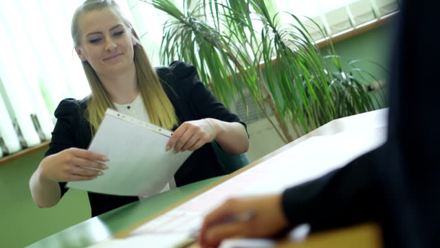 Candidate giving documents to interviewer at desk