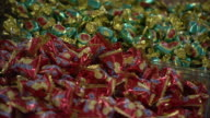 Candies with red wrappers and green wrappers fill a bin at a store in Tianjin, China.