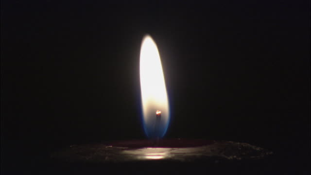 CU Candle against black background flickers until blown out / Long Island, New York, USA