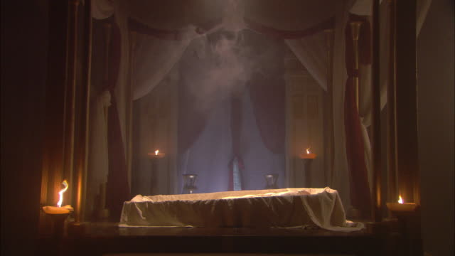 Candles illuminate the funeral bier of Cleopatra.