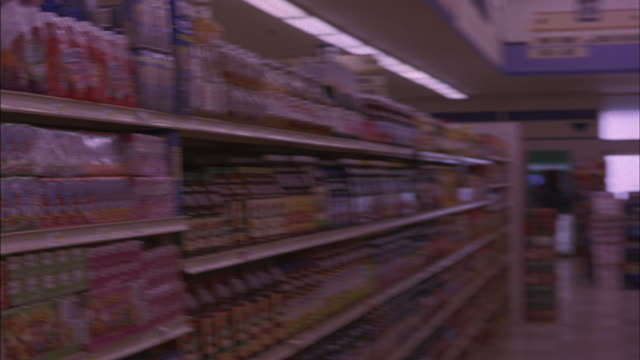 Canned vegetables and fruit juices are stacked neatly on shelves.
