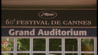 Preview Workmen laying red carpet on hotel steps Sign over entrance '60 Festival de Cannes' PULL OUT to red carpet in f/g Security officer and dog on...