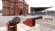 Cannons stand in front of the Pierhead Building and Senedd, home to the National Assembly for Wales. Available in HD.