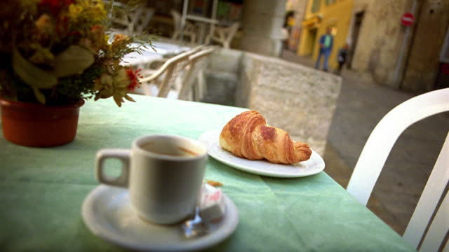 Canted close up pan coffee cup and croissant on outdoor table with village street in background / Provence, France