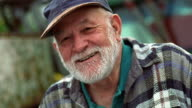 Canted close up portrait senior man with beard and baseball cap laughing outdoors / California