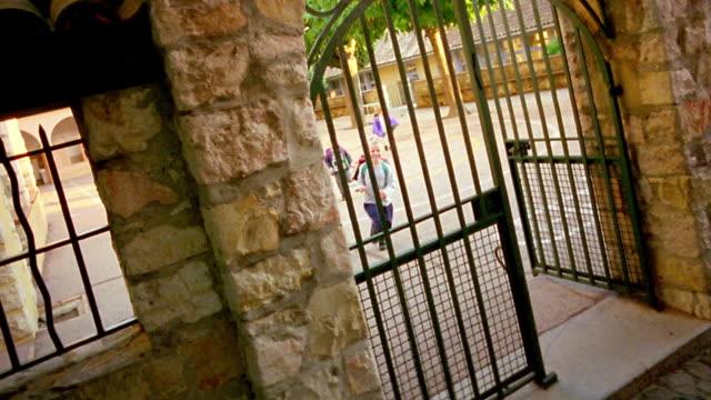 Canted high angle wide shot pan three schoolchildren running through gate and down cobblestone sidewalk/ Biot, France